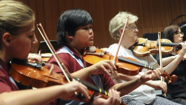 Goulburn Public School year five pupils Teesha Jones, left, and Brendell Guiao sit next to CSO first violinist Barbara Jane Gilby at a rehearsal for Tuesday's performance.