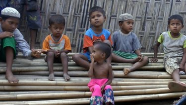 Rosmaida Bibi, foreground, sits on a pile of bamboo trees with other children of her age at the Dar Paing camp.