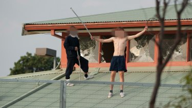 Youths protesting on the roof of the Melbourne Youth Justice Centre at Parkville in March.