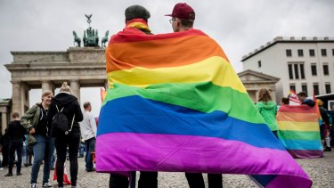 Men with rainbow flags stand in front of the Brandenburg Gate to celebrate the legalisation of same-sex marriage in Germany.