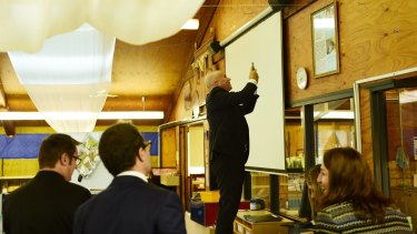 Adrian Piccoli photographs a story on a library wall about David Gonski's visit to Villawood North Public School.