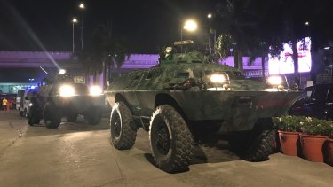 Military vehicles are positioned outside the Resorts World Manila.