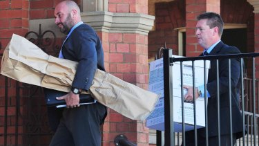 Detective Senior Constable John Cosgrove and Detective Sergeant Darren Gunn carry evidence into the Wagga courthouse, including what is believed to have been a shotgun involved in the deaths of the Hunt family.