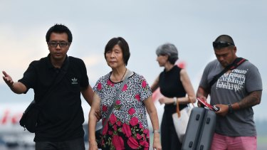 Australian Consulate staff assist Helen Chan, the mother of Bali Nine member Andrew Chan, followed by his brother Michael Chan as they arrived at Yogyarkarta airport on Thursday.