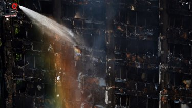 The sun creates a rainbow effect as firefighters work at the scene of a deadly blaze on June 14.