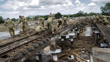 Soldiers from 8th/9th RAR, and engineers from 2nd CER, clear the train line that runs through Grantham, Queensland, after flooding in 2011.