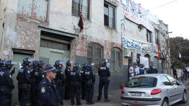 Police in riot gear as the first door at the Hat Factory is destroyed.