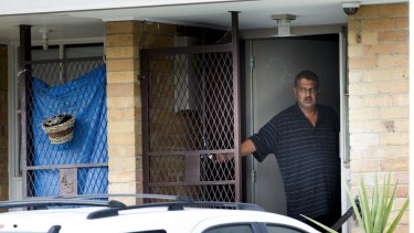 A man looks on to the street full of waiting media from his Heidelberg West home.