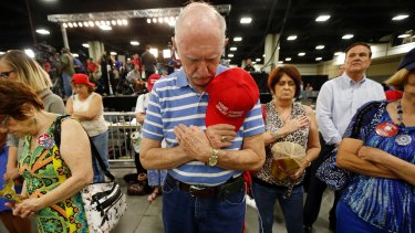 Supporters bow their heads in prayer before Republican presidential candidate Donald Trump delivers a campaign speech in Charlotte, North Carolina.