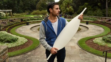 Artist Jonathan Jones holds one of the 15,000 ceramic Aboriginal shields that will outline the lost Garden Palace in the Royal Botanic Gardens.