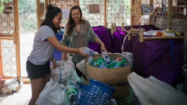 Melati and Isabel sorting plastic bags and bottles.
