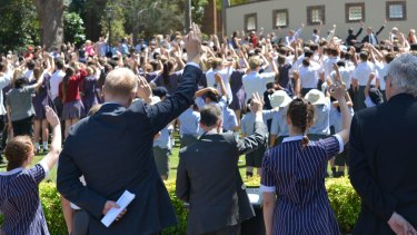 """Students make a sign symbolising """"B"""" for Barker at the school assembly on Friday."""