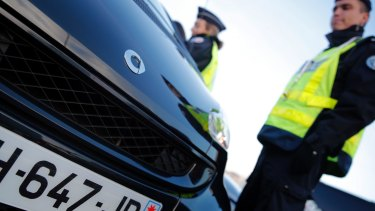 Police officers check cars as Paris suffers a pollution spike.
