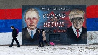 People walk by Serb nationalist graffiti depicting Russian President Vladimir Putin and US President Donald Trump in Belgrade.