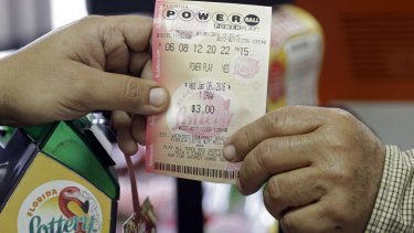 A clerk hands over a Powerball ticket to a customer at a grocery store in Florida.