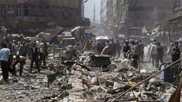 People inspect a site hit by what activists said were air strikes by forces loyal to Syria's President Bashar al-Assad on a marketplace in Douma on Sunday.