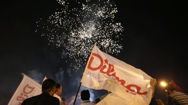 Militants of the Workers Party watch fireworks in support of Rousseff in Brasilia, during transmission of the Workers Party's TV program.