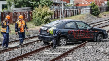 Workers prepare to tow the protesters' car from the tracks at Ascot Vale.
