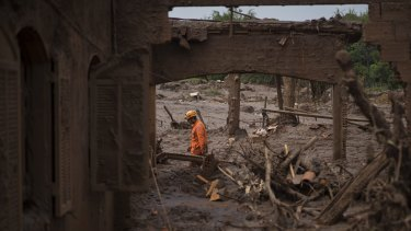 A rescue worker walks between destroyed houses in the town of Bento Rodrigues after the Fundao dam burst in Minas Gerais, Brazil.