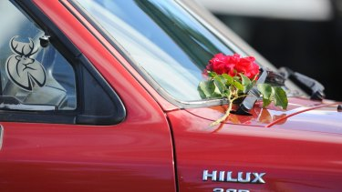 A floral tribute is laid on a 4WD out the front of the home.
