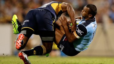 Down you go: Kurtley Beale of the Waratahs is upended by Tevita Kuridrani of the Brumbies.