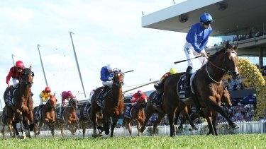 Rise for the Rose: Jockey James McDonald stands up in the irons as he crosses the line to win the Golden Rose on Astern.