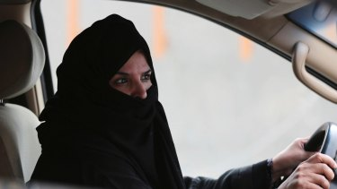 A woman drives a car on a highway in Riyadh.