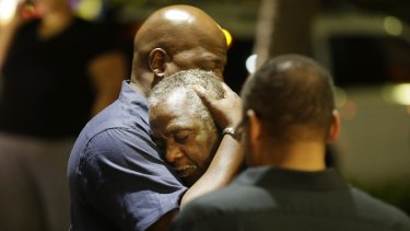 Worshippers embrace following a group prayer across the street from the scene of a shooting Wednesday.