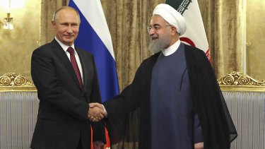 Irania President Hassan Rouhani, right, welcomes Russian President Vladimir Putin to the Saadabad Palace in Tehran on Wednesday.