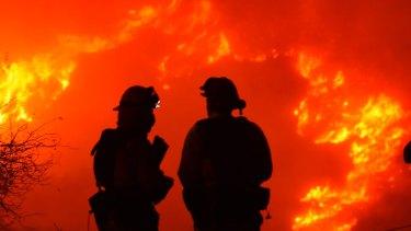 Santa Barbara firefighters keep a close eye on nearby flames atop Shepard Mesa Road in Carpinteria, California on Sunday.