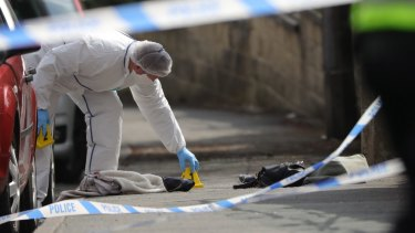 Forensic police examine shoes and a handbag at the scene.