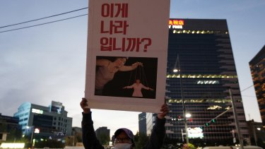 """A protester holds a placard showing South Korean President Park Geun-hye as a puppet with the words """"This is not a country"""" during a massive protest on Saturday in Seoul."""