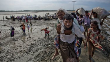 A Rohingya Muslim man from Myanmar carries an elderly woman after they crossed the border into Bangladesh from Myanmar last month.