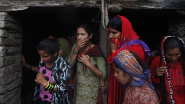 Nepalese women react after rescuers recovered a dead body of a victim from the debris after a landslide in Lumle village.