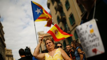 A woman holds a Spanish flag in support of  police as pro-independence protesters gather in front of the national police headquarters in Barcelona on October 3.