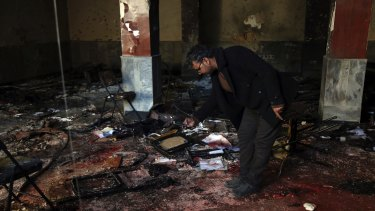 An Afghan man takes a photograph at the scene of a suicide attack on a Shiite cultural center in Kabul.