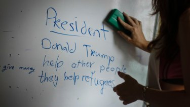 A volunteer teacher erases the board after her English lesson to Christian Burmese refugees in Kuala Lumpur, Malaysia.