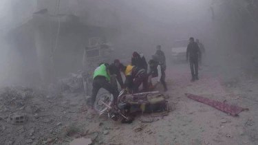 White Helmets carry an injured man after government air strikes hit Douma, near Damascus, Syria, on Sunday.