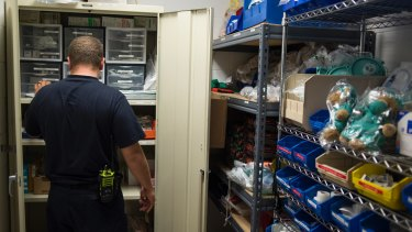 Doug Rolf, a firefighter and medic restocks medicine after responding to an overdose, in Colerain, Ohio.