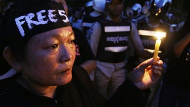 A demonstrator holds a candle in support of detained human rights activists in Phnom Penh on Monday.