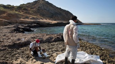 Members of the Libyan Red Crescent retrieve the body of a migrant from the shore of the Mediterranean Sea, east of Tripoli, Libya, on Monday.