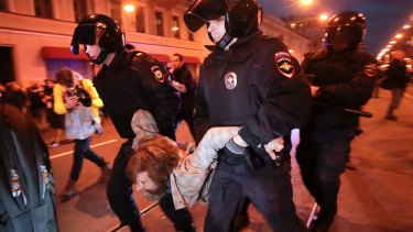 Riot police officers detain a protester during a rally in St. Petersburg.