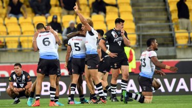 Winners and losers: Fiji celebrate their historic win over New Zealand.
