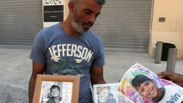 Tahar Mejri holds photographs of his 4-year-old son, Kylan.