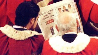 Members of the House of Lords read a newspaper article about Labour women MPs' fashion sense before the Queen delivers her speech in 1997.