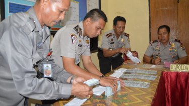 Police officers displaying six stacks of $US100 bills during a press conference by Nusa Tenggara Timur police chief Endang Sunjaya at Rote police station in June.