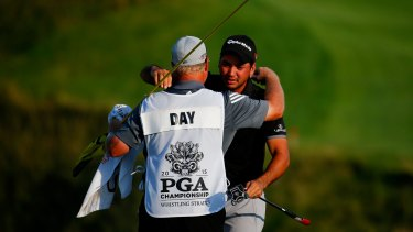 At last: Jason Day celebrates with his caddie Colin Swatton.