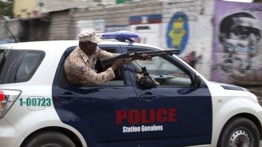 A police officer fires at demonstrators in Port-au-Prince.