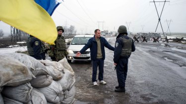 Ukrainian soldiers check passengers of a car at a checkpoint in the eastern Ukrainian city of Kurakhove, near Donetsk, as heavy fighting raged on Wednesday.