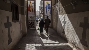 Coptic Christians walk outside St Mark's Church in Minya, south of Cairo.